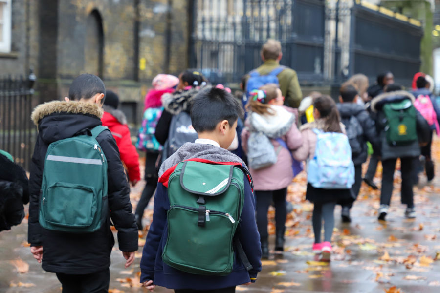 children with green backpacks on their way to school