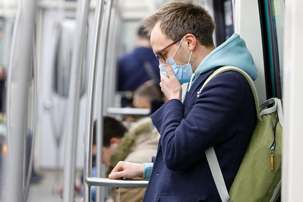 Young man an on a London tube wearing a mask to protect him from coronavirus