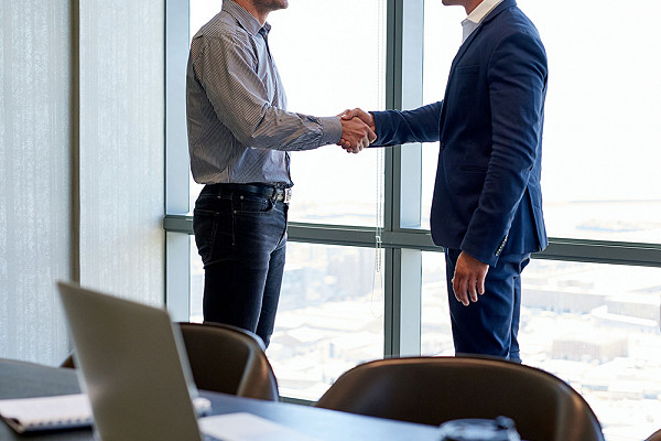 two men shaking hands in a meeting