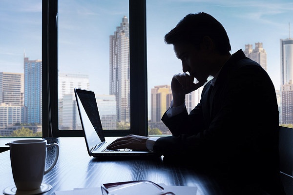Silhouette of man looking at a laptop in an office